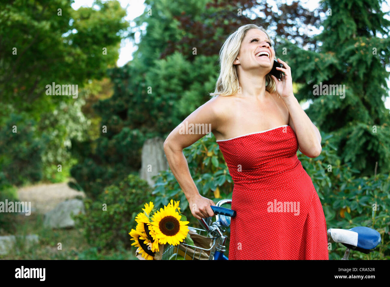 Woman talking on cell phone on bicycle - Stock Image