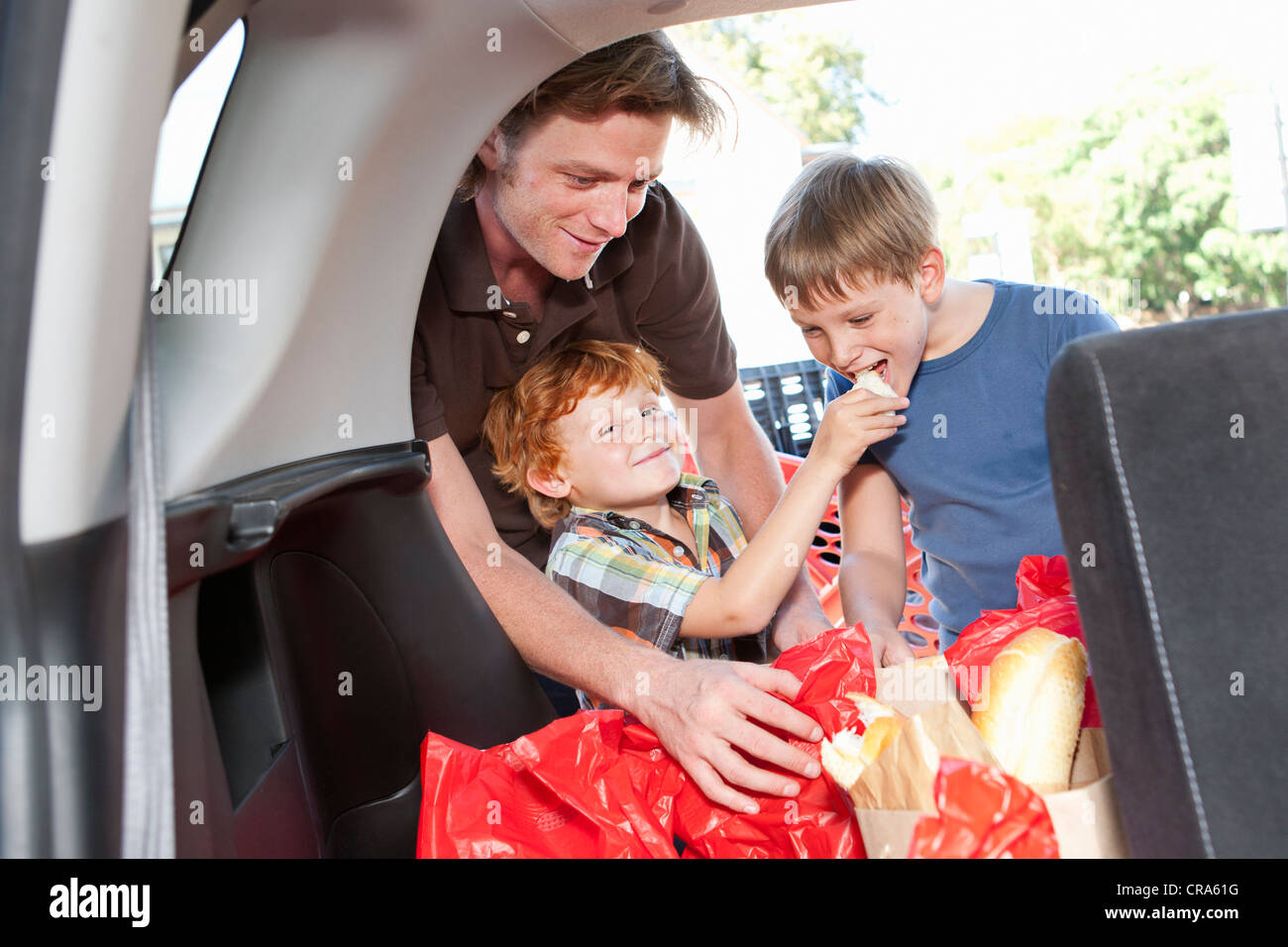Boys eating groceries in trunk of car - Stock Image