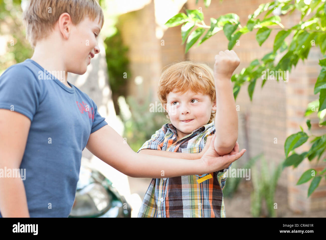 Boy feeling brothers biceps outdoors - Stock Image