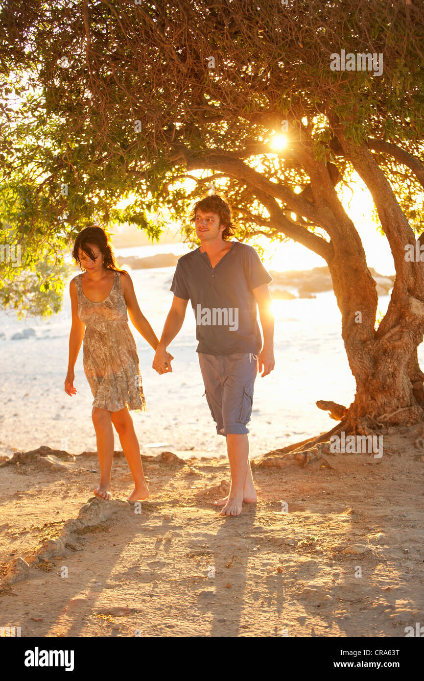 Couple walking barefoot in park - Stock Image