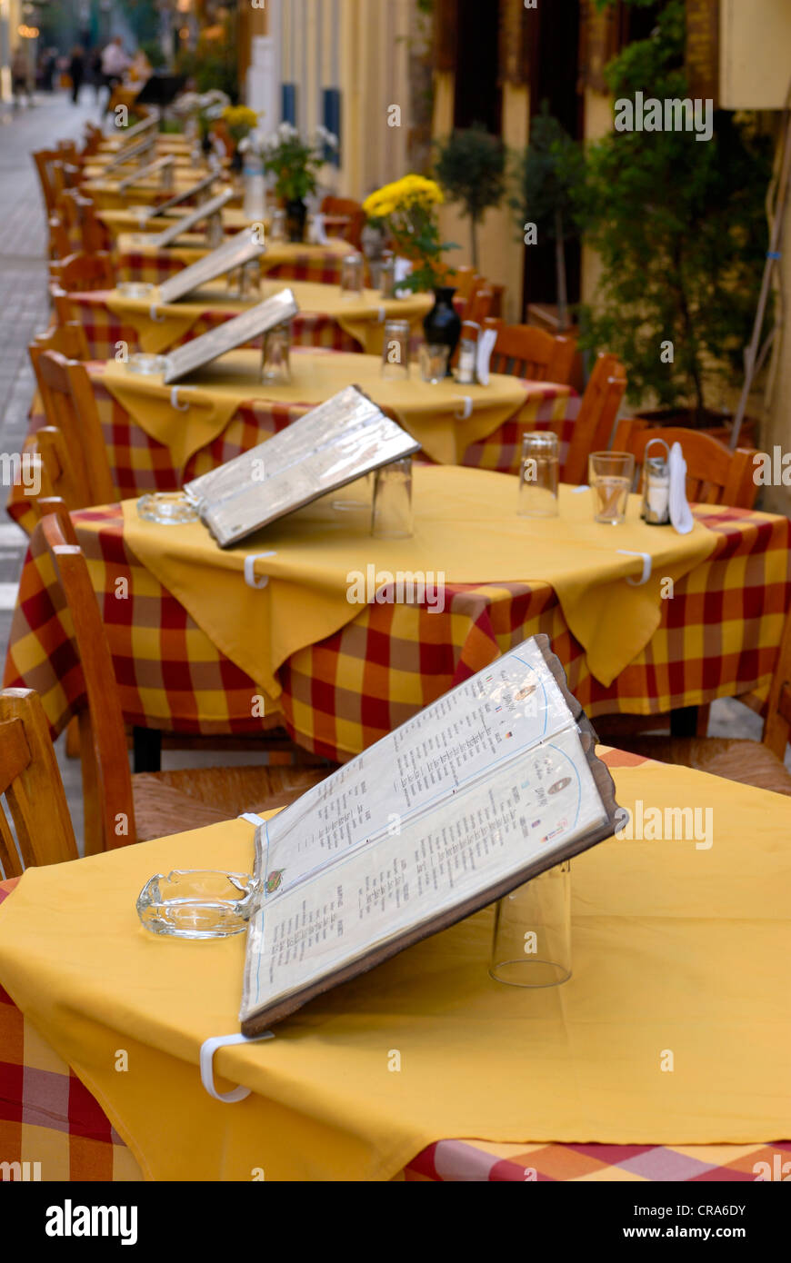 Tables with menus in a row, stree restaurant in Nafplion, Peloponnese, Greece, Europe - Stock Image