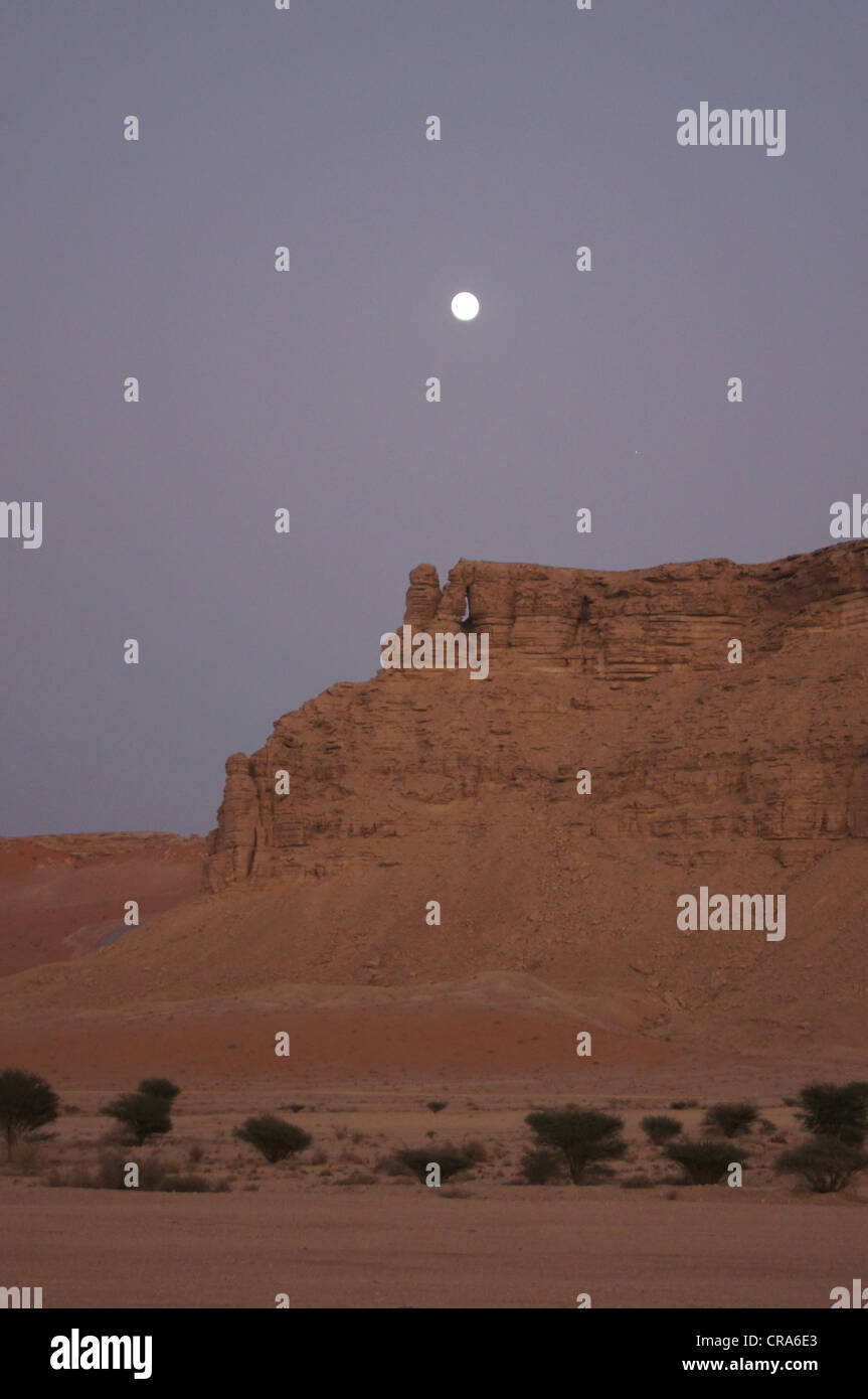 The moon coming out over rock formations in the Red Sands desert - Riyadh, Kingdom of Saudi Arabia - Stock Image