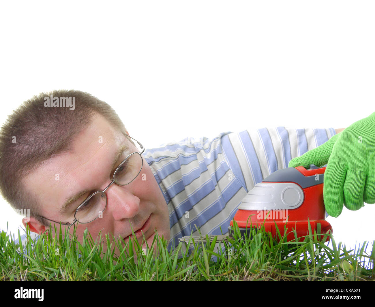 Young man trimming fresh grass with trimmer - Stock Image