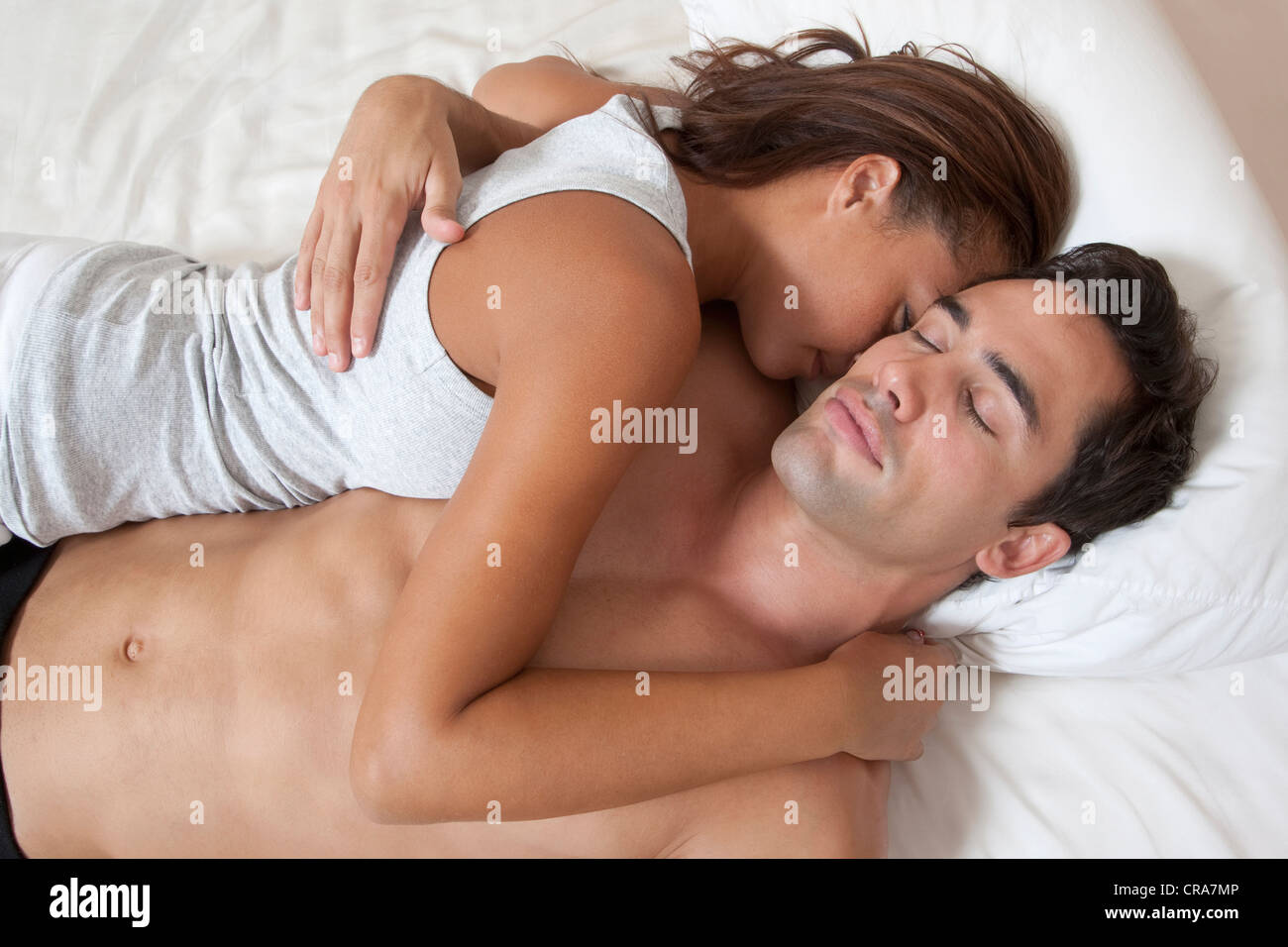 Couple sleeping in bed together - Stock Image
