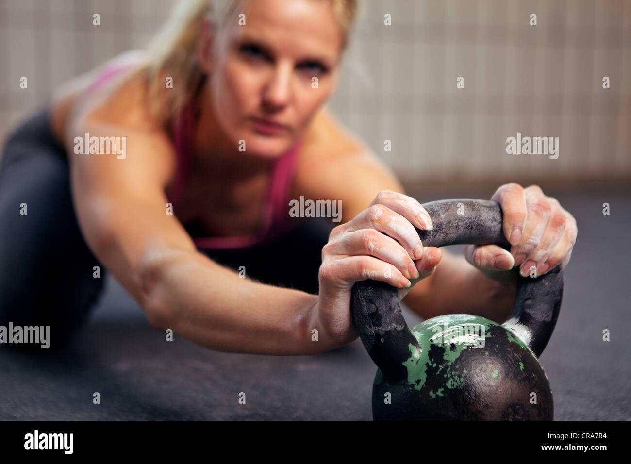 Portrait of young woman having a short break in her kettlebell crossfit workout - Stock Image
