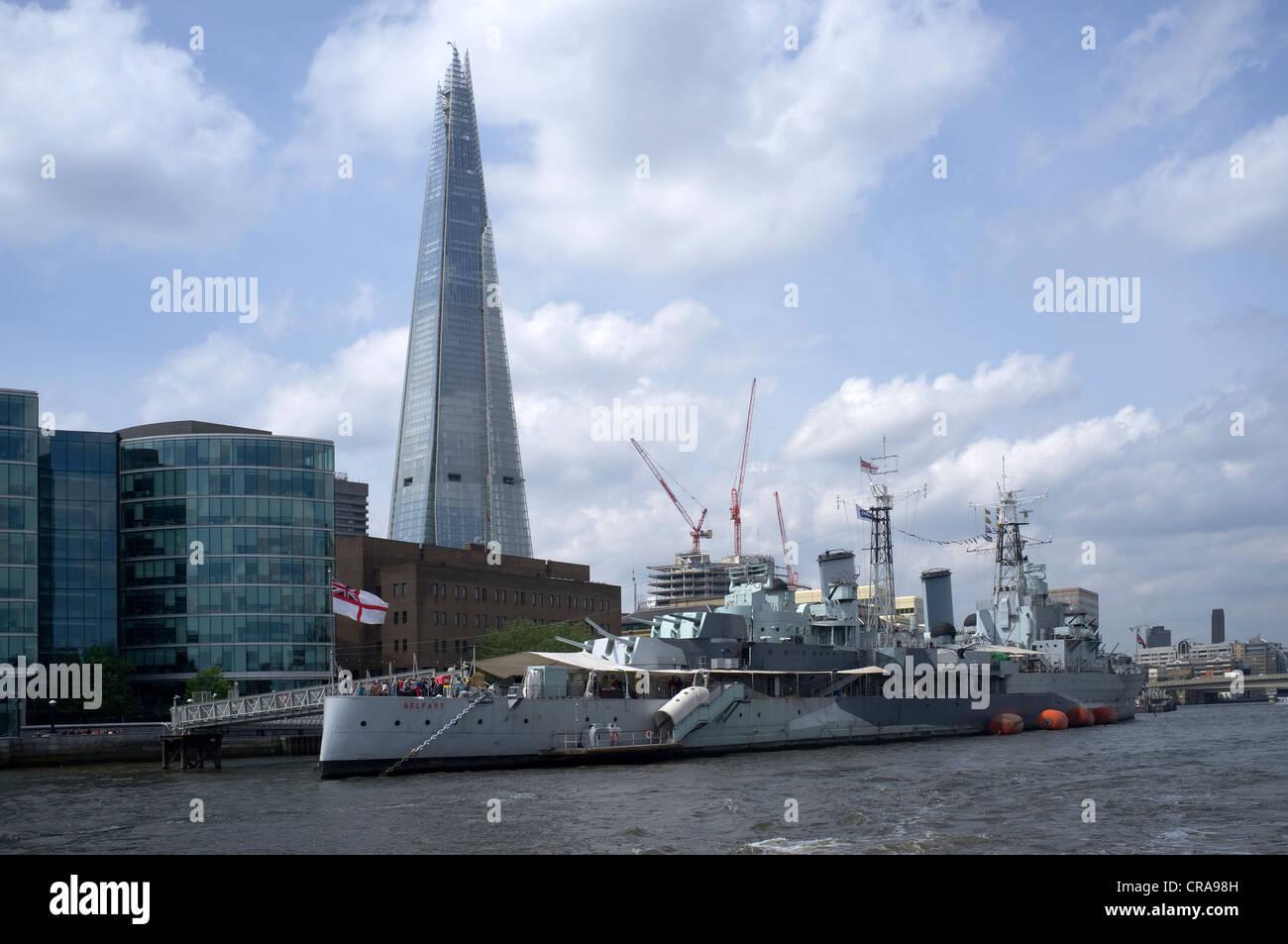 HMS Belfast Moored alongside Shard of Glass between London Bridge and Tower Bridge -1 - Stock Image