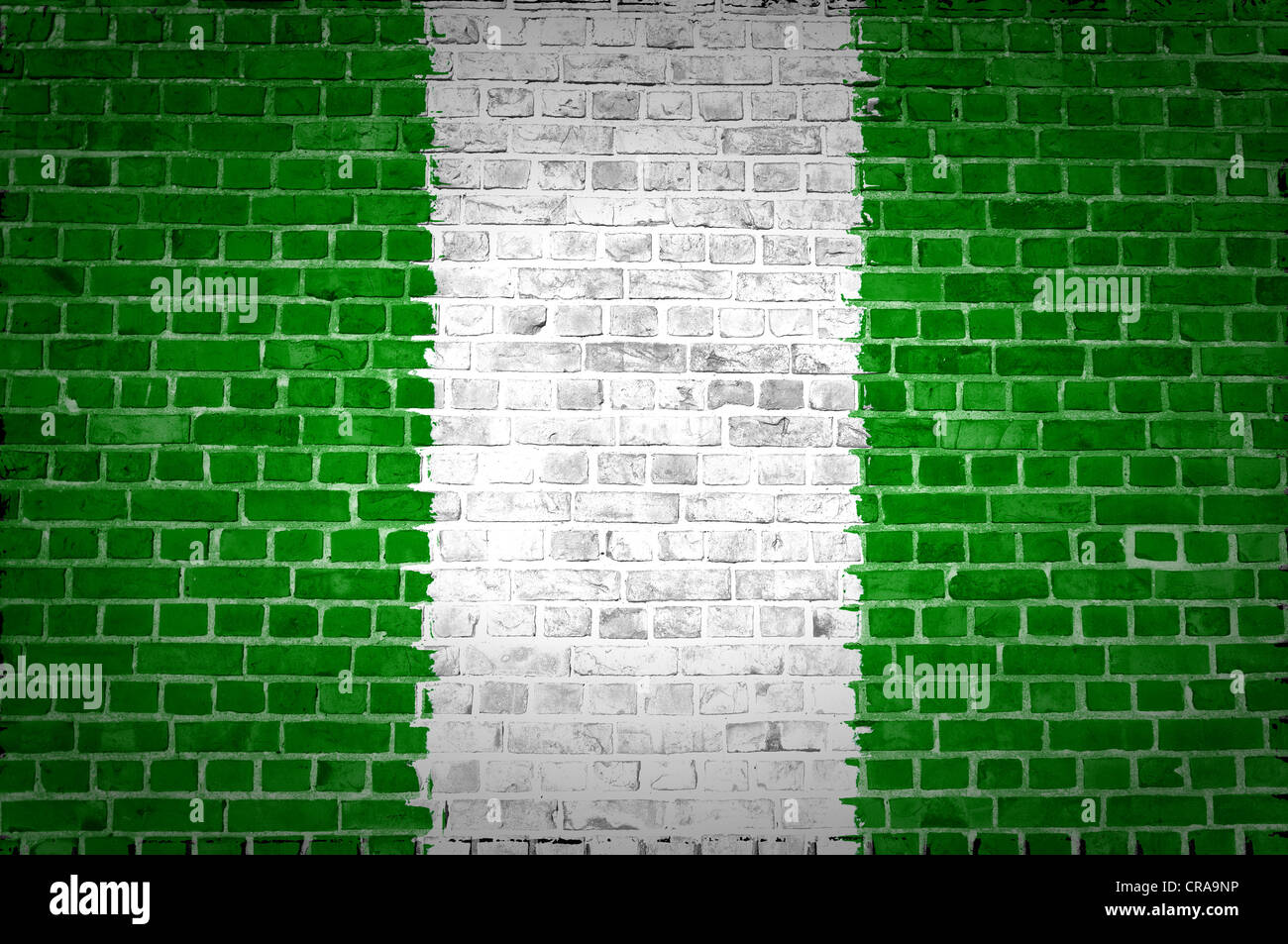An image of the Nigeria flag painted on a brick wall in an urban location - Stock Image