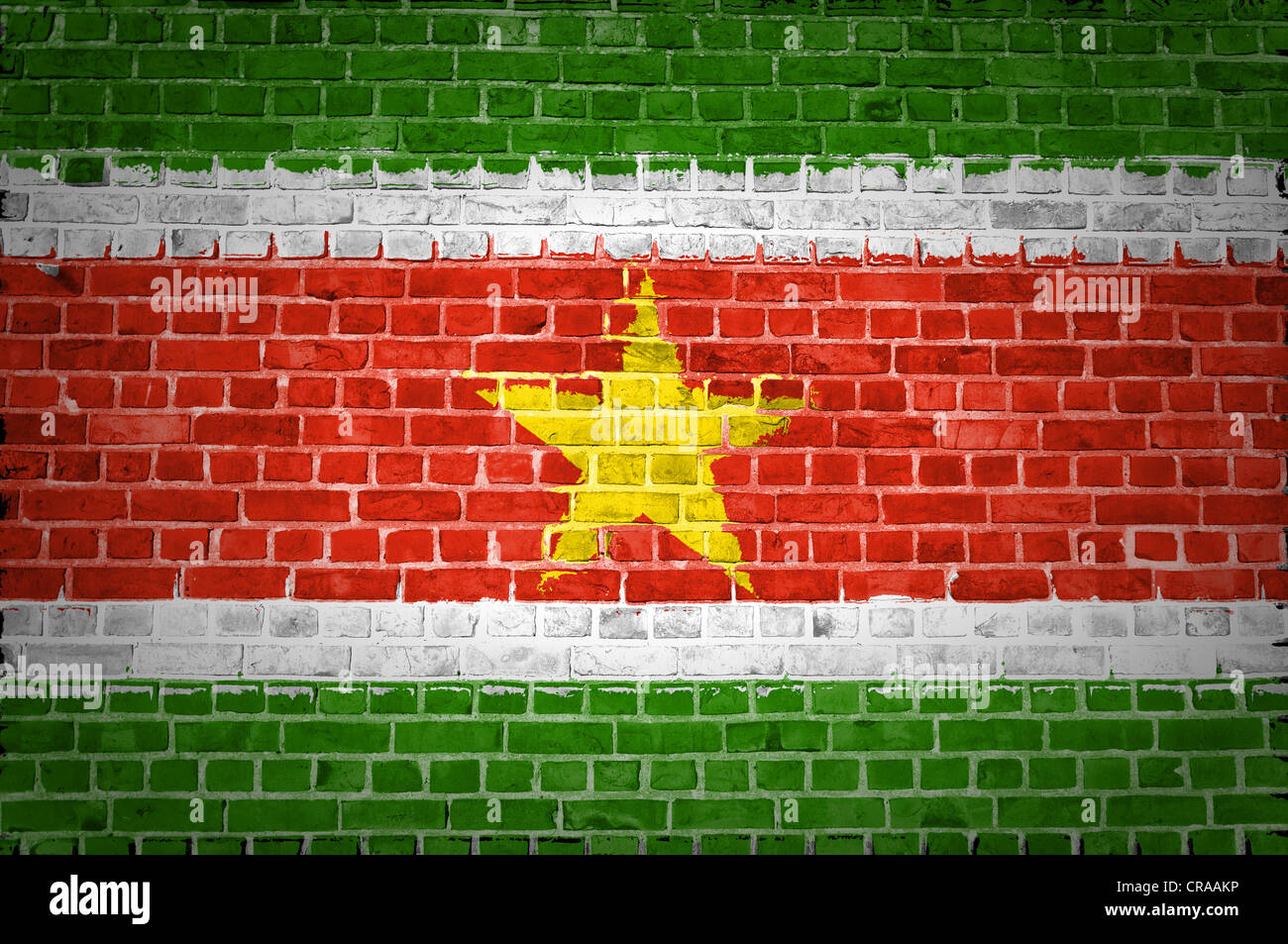 An image of the Suriname flag painted on a brick wall in an urban location - Stock Image