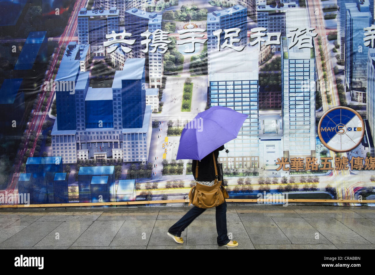 Woman walks past billboard showing planned future layout of Central Business District CBD in Beijing China - Stock Image