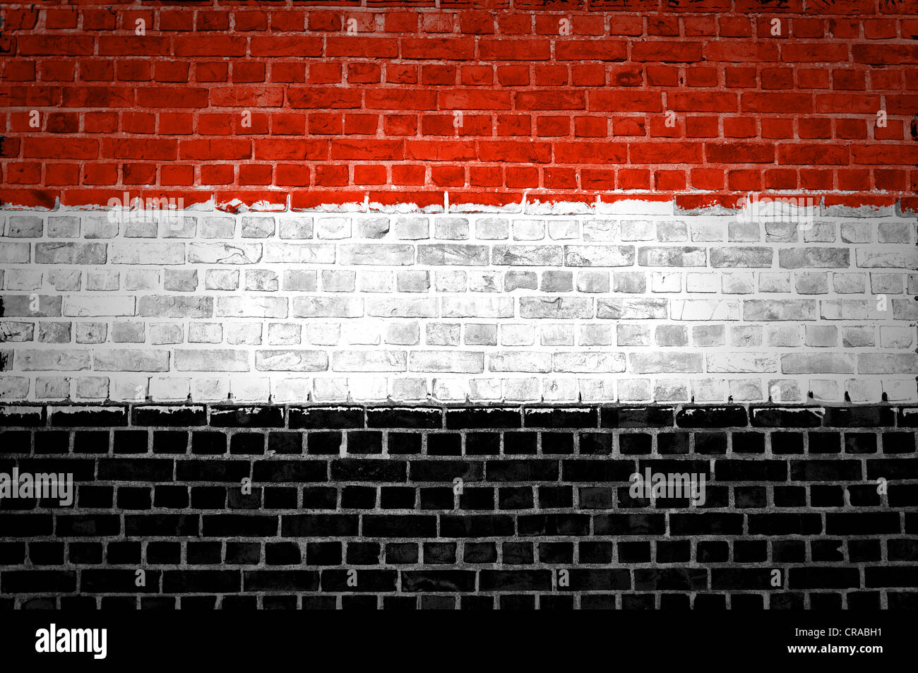 An image of the Yemen flag painted on a brick wall in an urban location - Stock Image