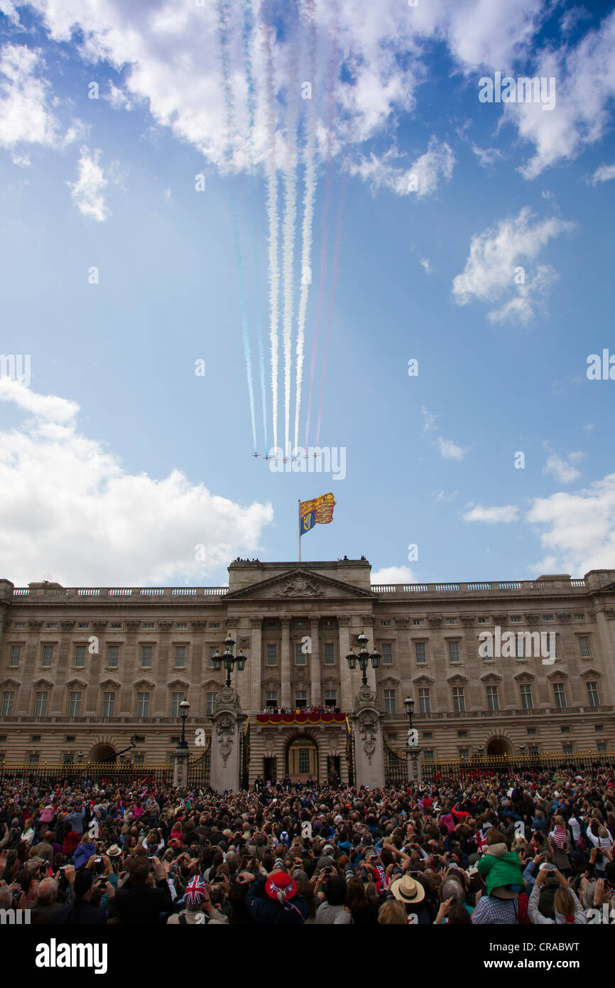 The Red Arrows display team fly past Buckingham Palace with the royal family on the balcony at Trooping the Colours - Stock Image