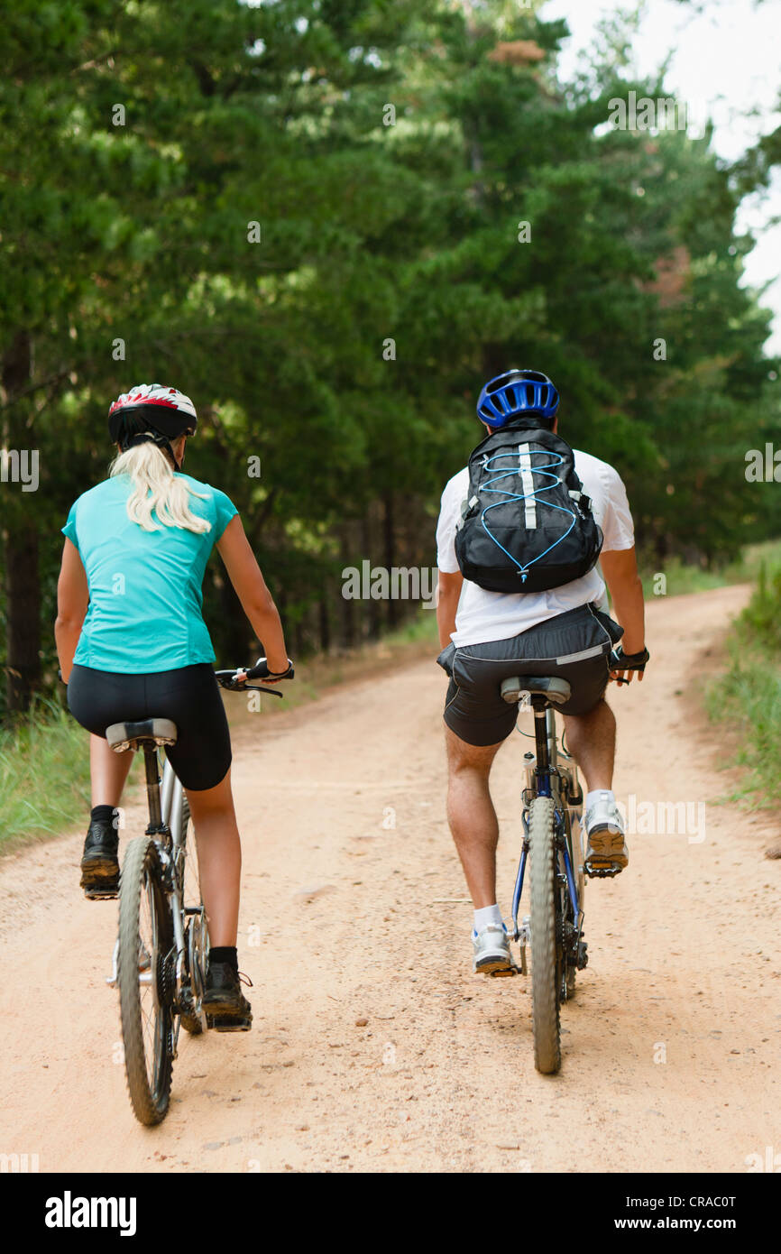 Couple mountain biking on dirt road - Stock Image