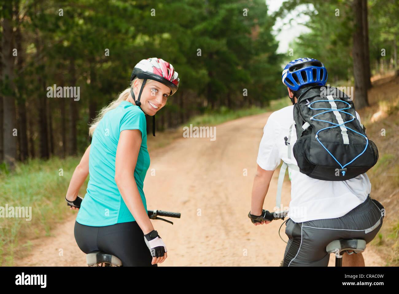 Couple mountain biking on dirt road - Stock Image