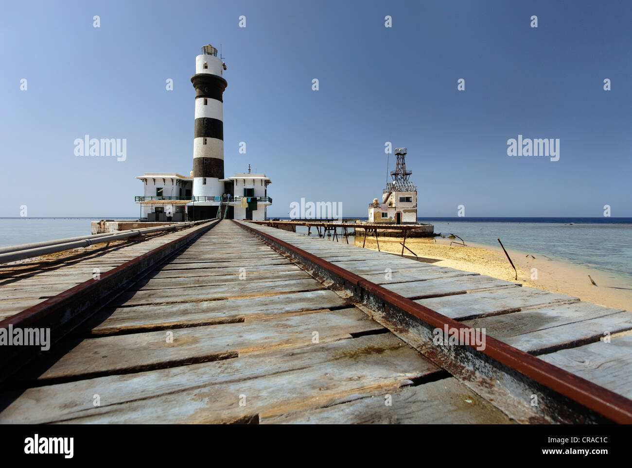 Rails, lighthouse with adjoining building, jetty and reef top, Daedalus Reef, Egypt, Red Sea, Africa - Stock Image