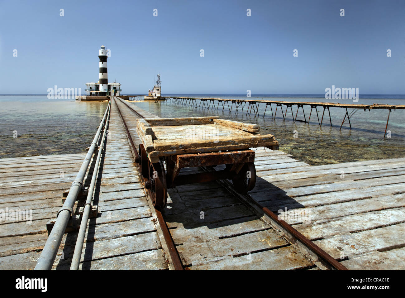 Trolley, rail car and rails, lighthouse with adjoining building, jetty and reef top, Daedalus Reef, Egypt, Red Sea, - Stock Image