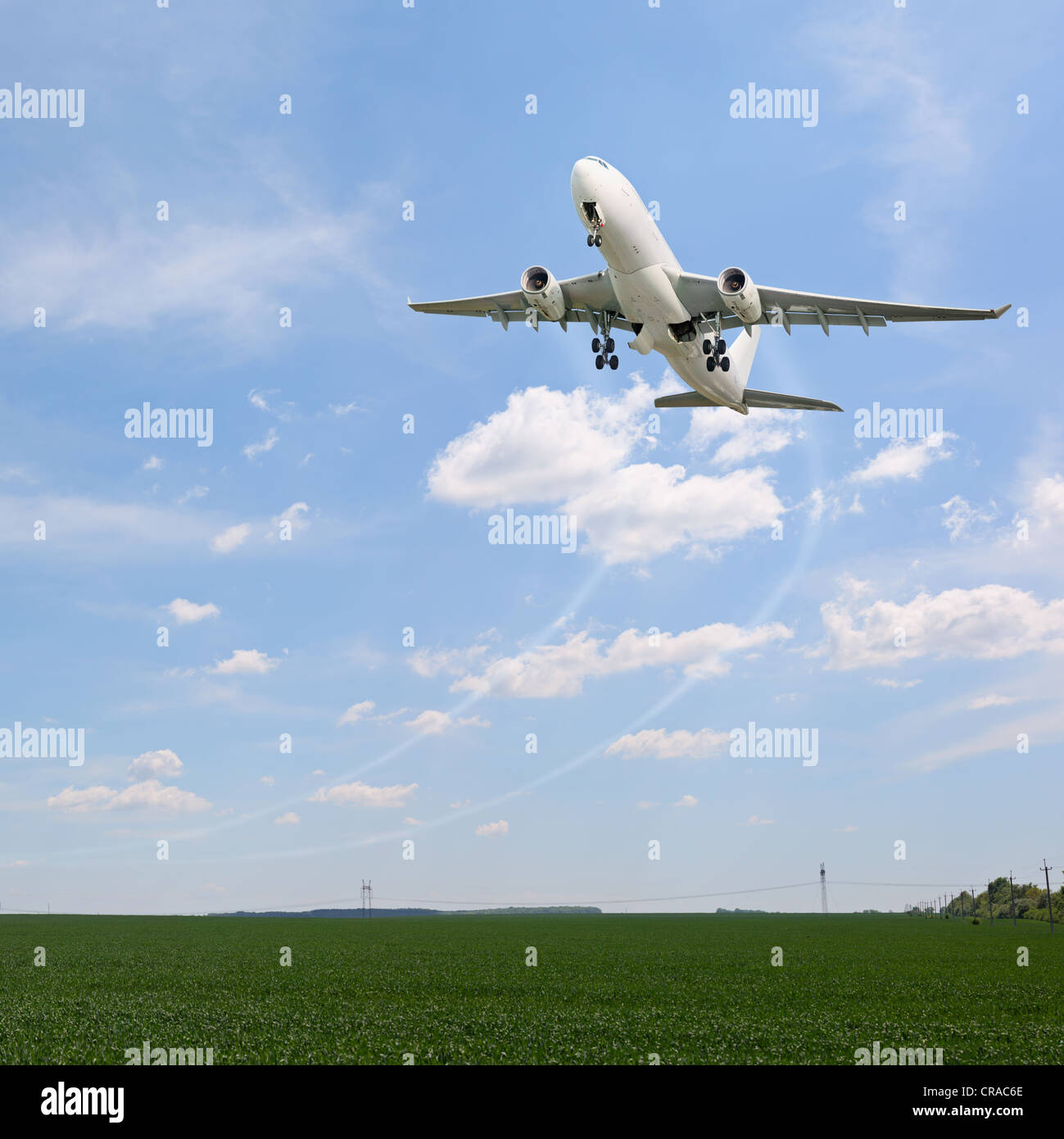 Passenger aircraft taking off over the fields - Stock Image