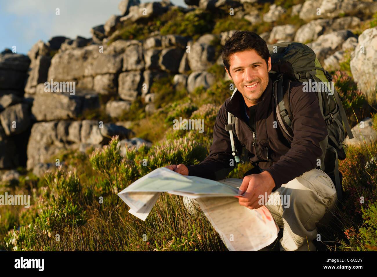 Hiker reading map in rocky field - Stock Image