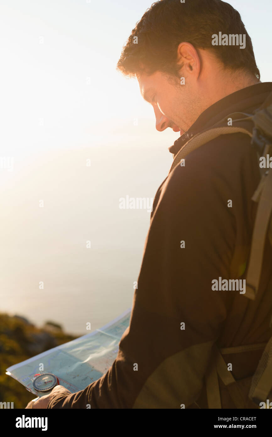 Hiker reading map outdoors - Stock Image