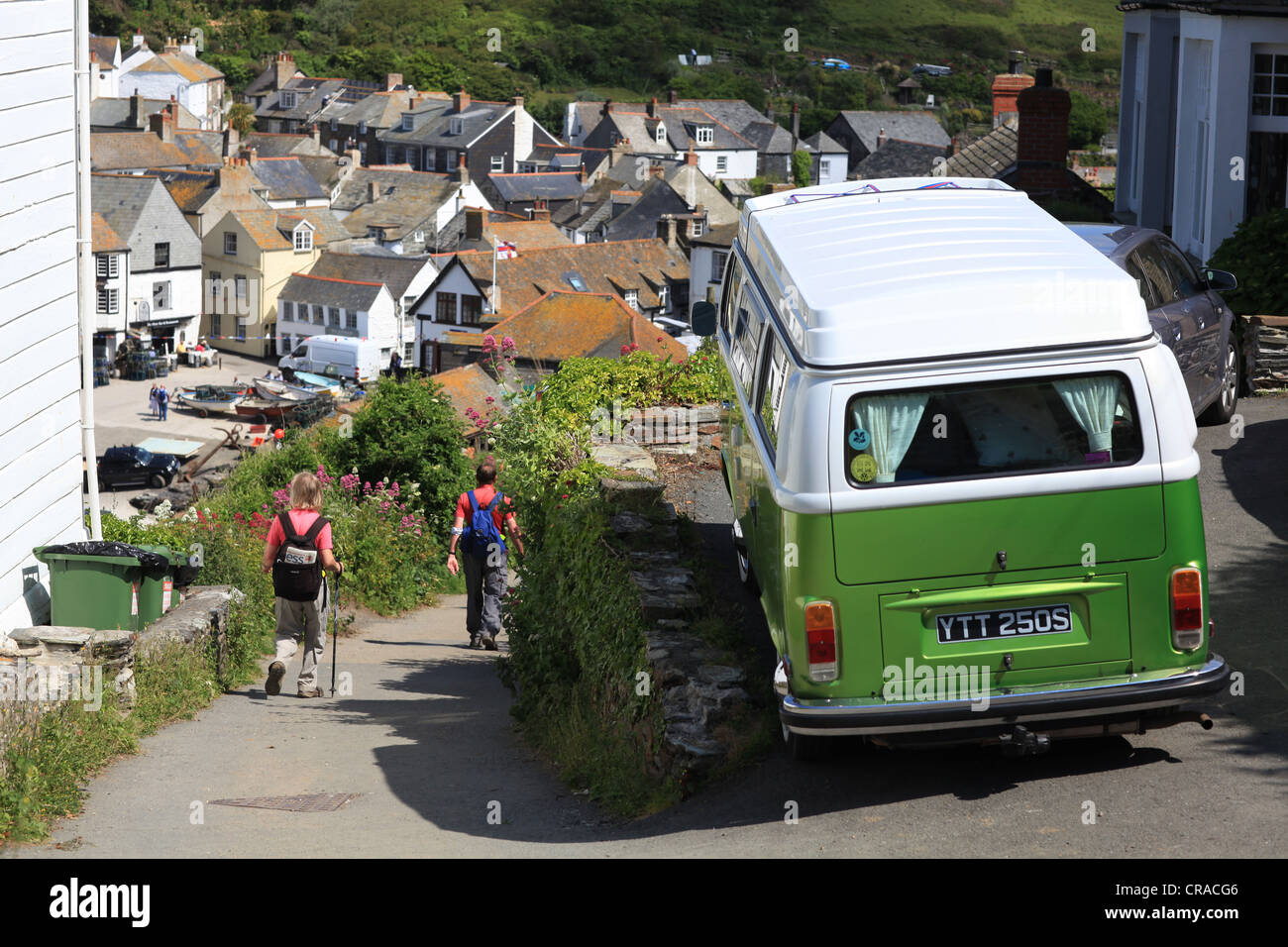 Port Isaac, North Cornwall, a VW camper van parked on a  narrow street with hikers and walkers heading for the seaside - Stock Image
