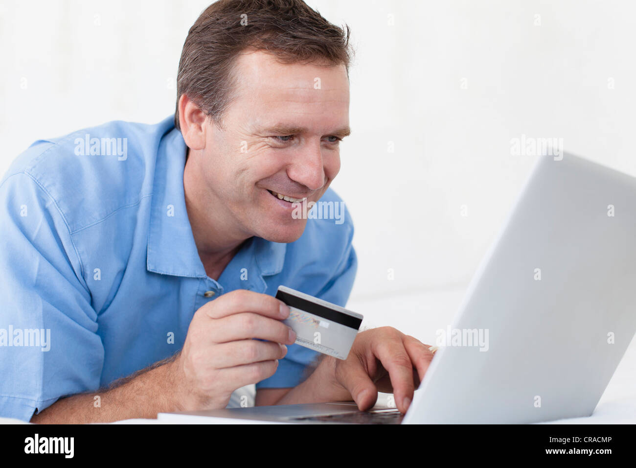 Man shopping online on bed - Stock Image
