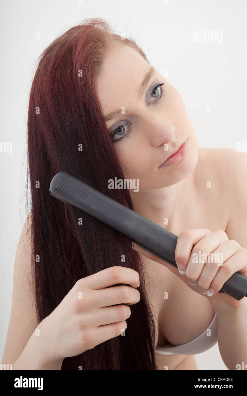 Young woman close shot using hair straighteners - Stock Image
