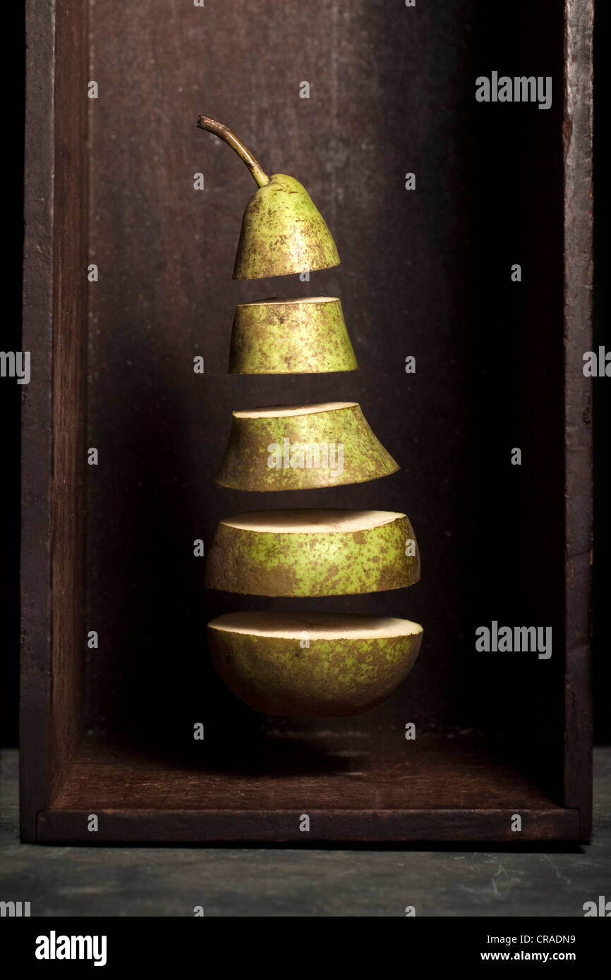 A pear that is divided into section and appears to be floating in a wooden box on a slate surface. - Stock Image