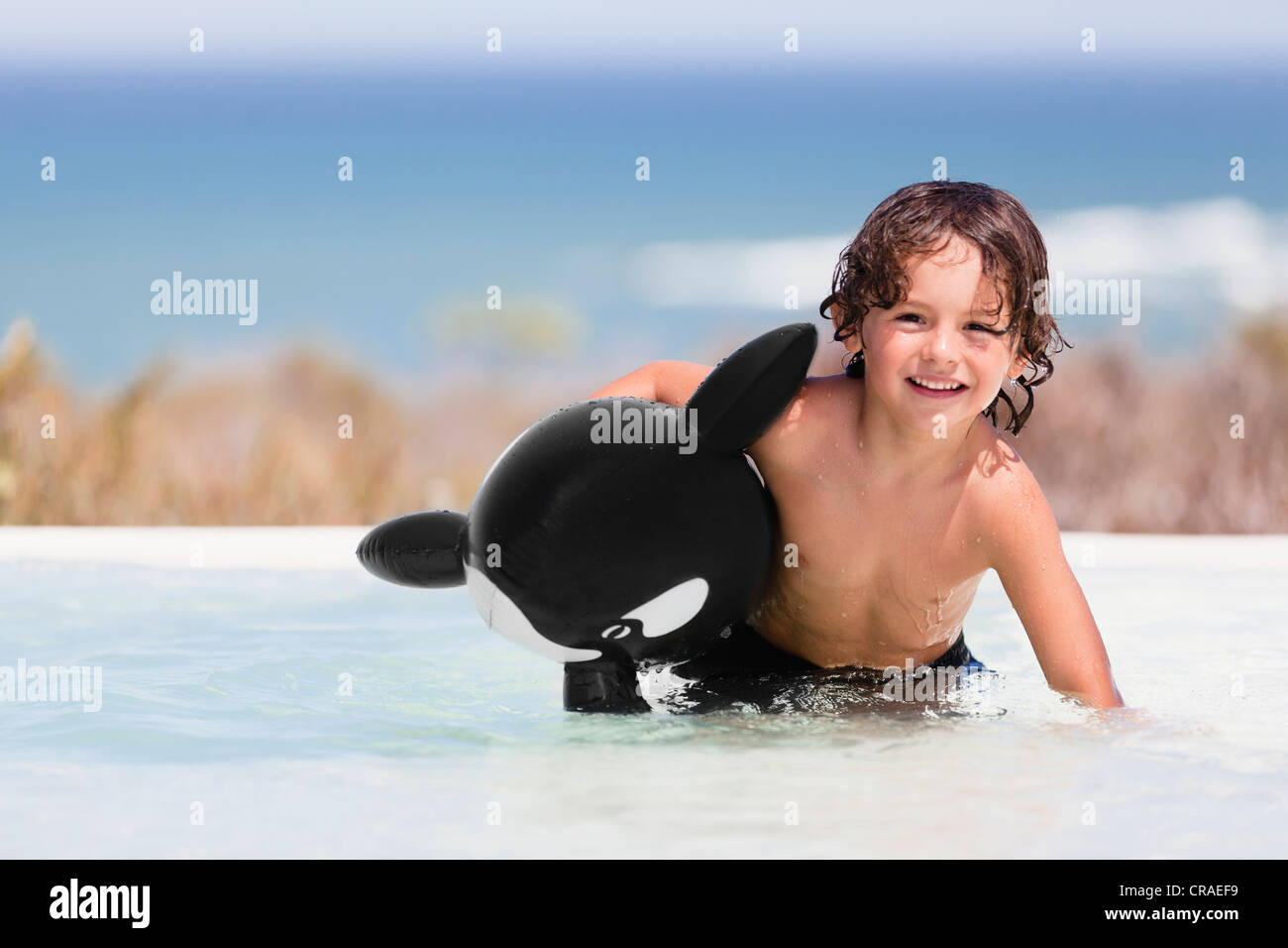 Boy playing with toy whale in pool - Stock Image
