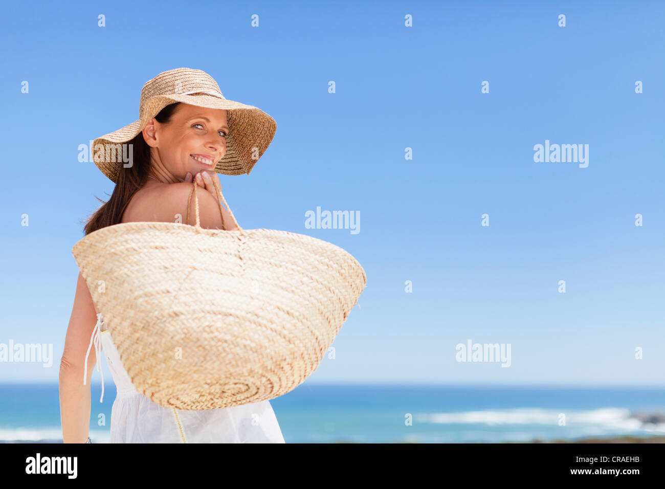 Woman carrying straw bag outdoors - Stock Image