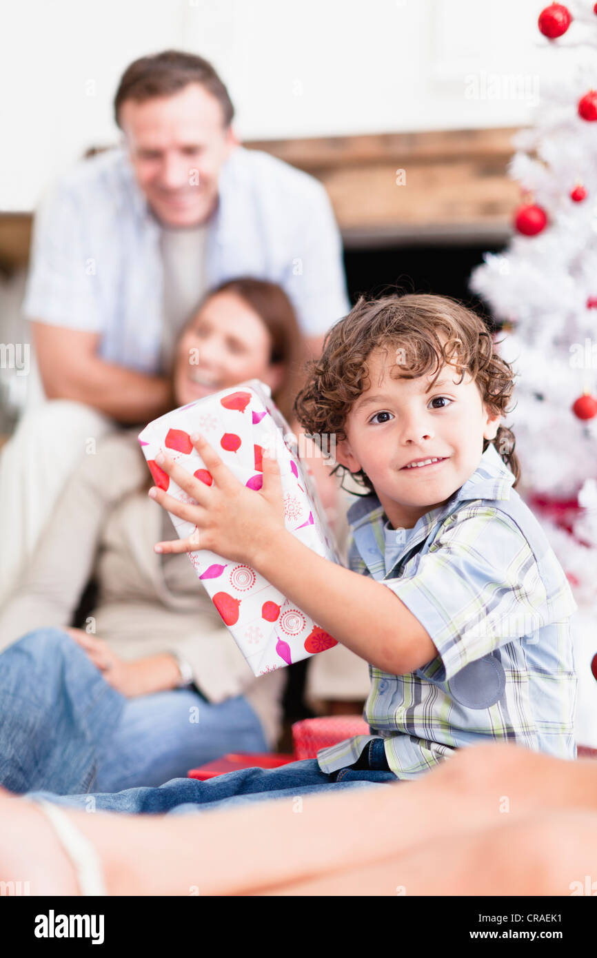 Boy shaking wrapped Christmas gift Stock Photo