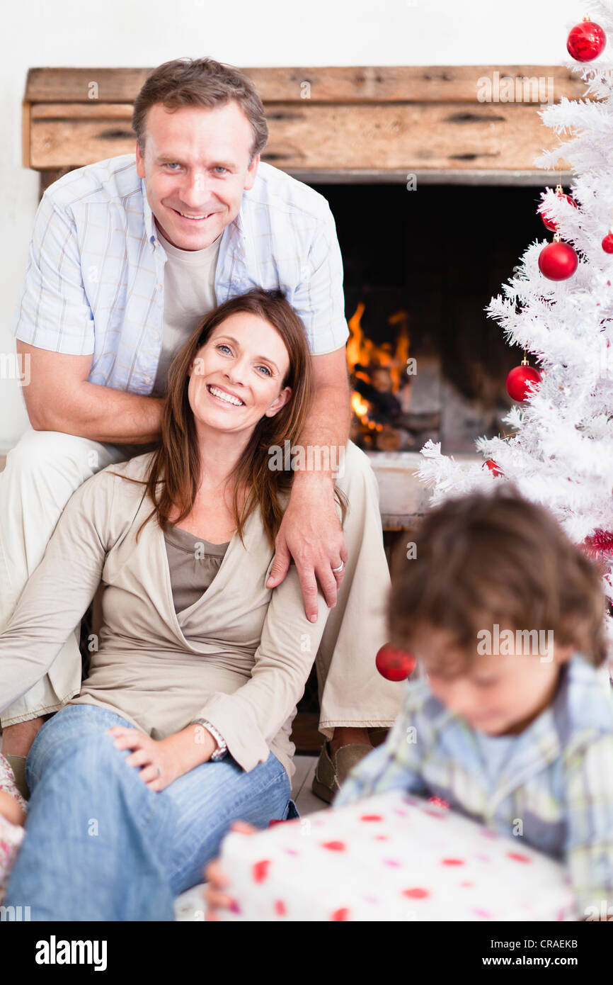 Couple relaxing by Christmas tree Stock Photo