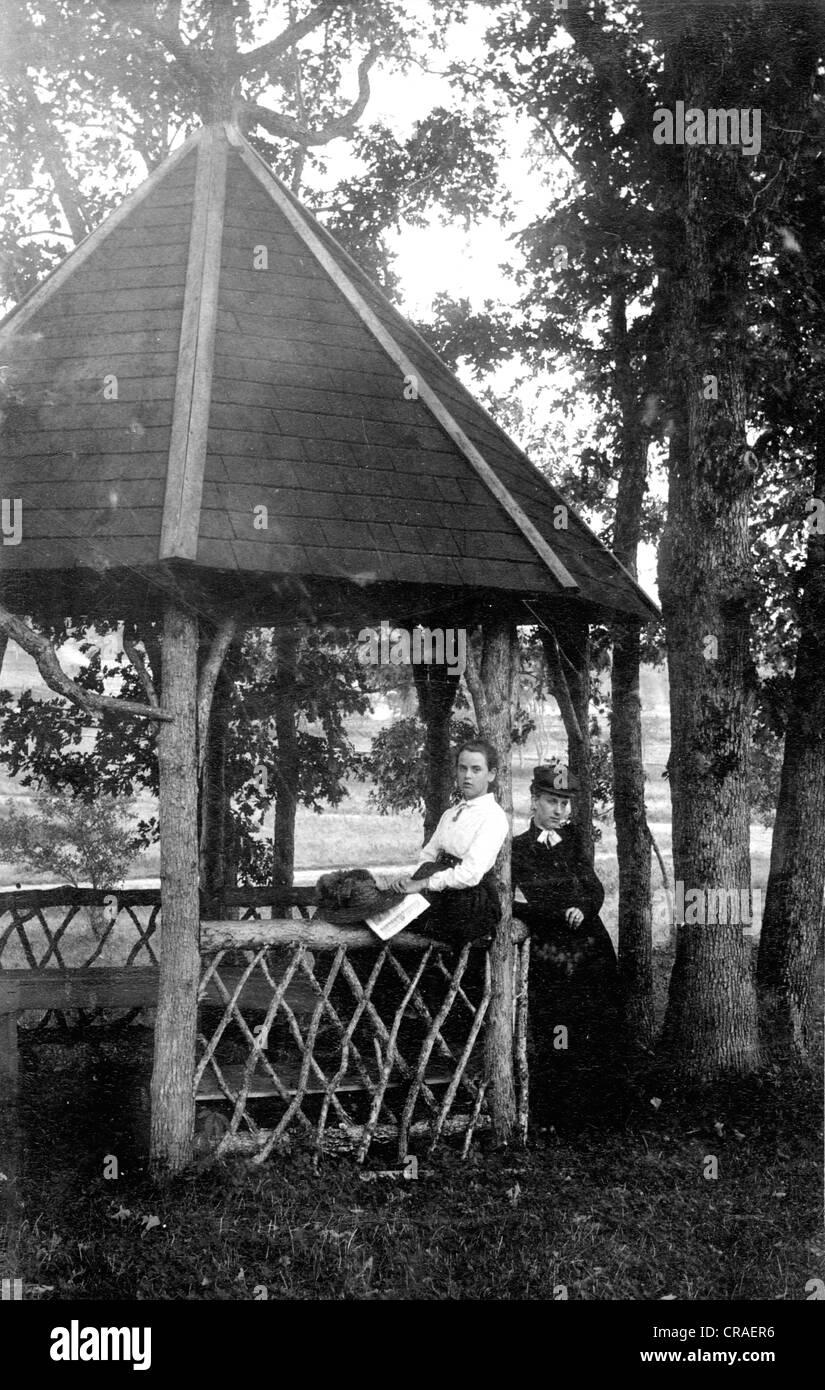 Two Victorian Girls at Rustic Gazebo - Stock Image