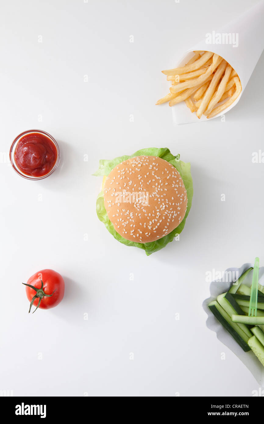 Fast food, burger, fries, ketchup, tomato, cucumbers - Stock Image