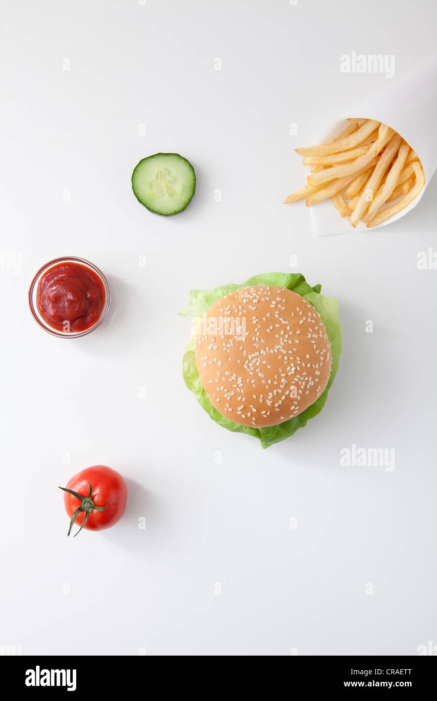 Fast food, burger, fries, ketchup, tomato, slice of cucumber - Stock Image