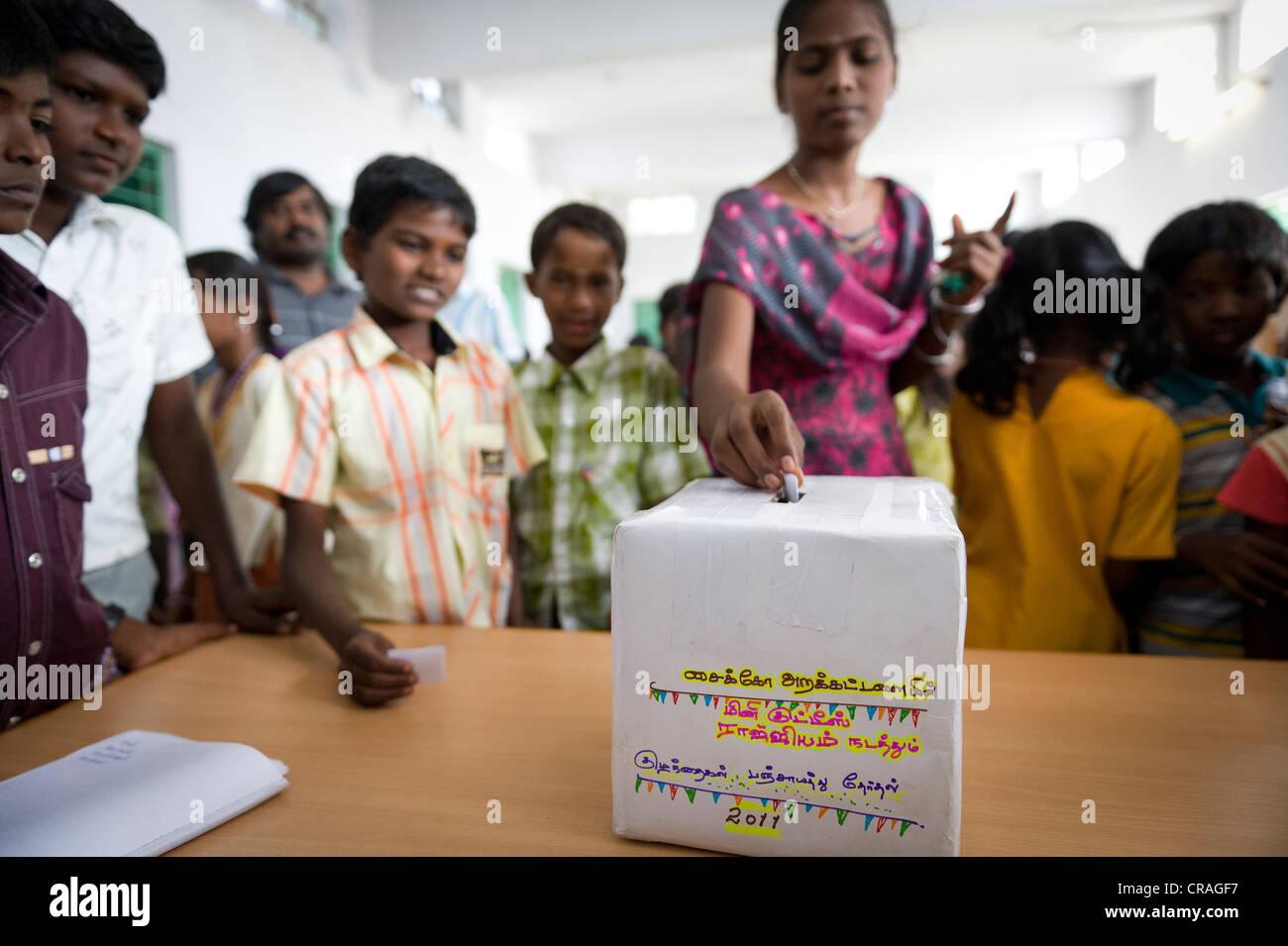 Girl putting ballot into voting box, mini Kutties Rajiyam, panchayat election, Noyyal Maravapalayam near Karur, - Stock Image