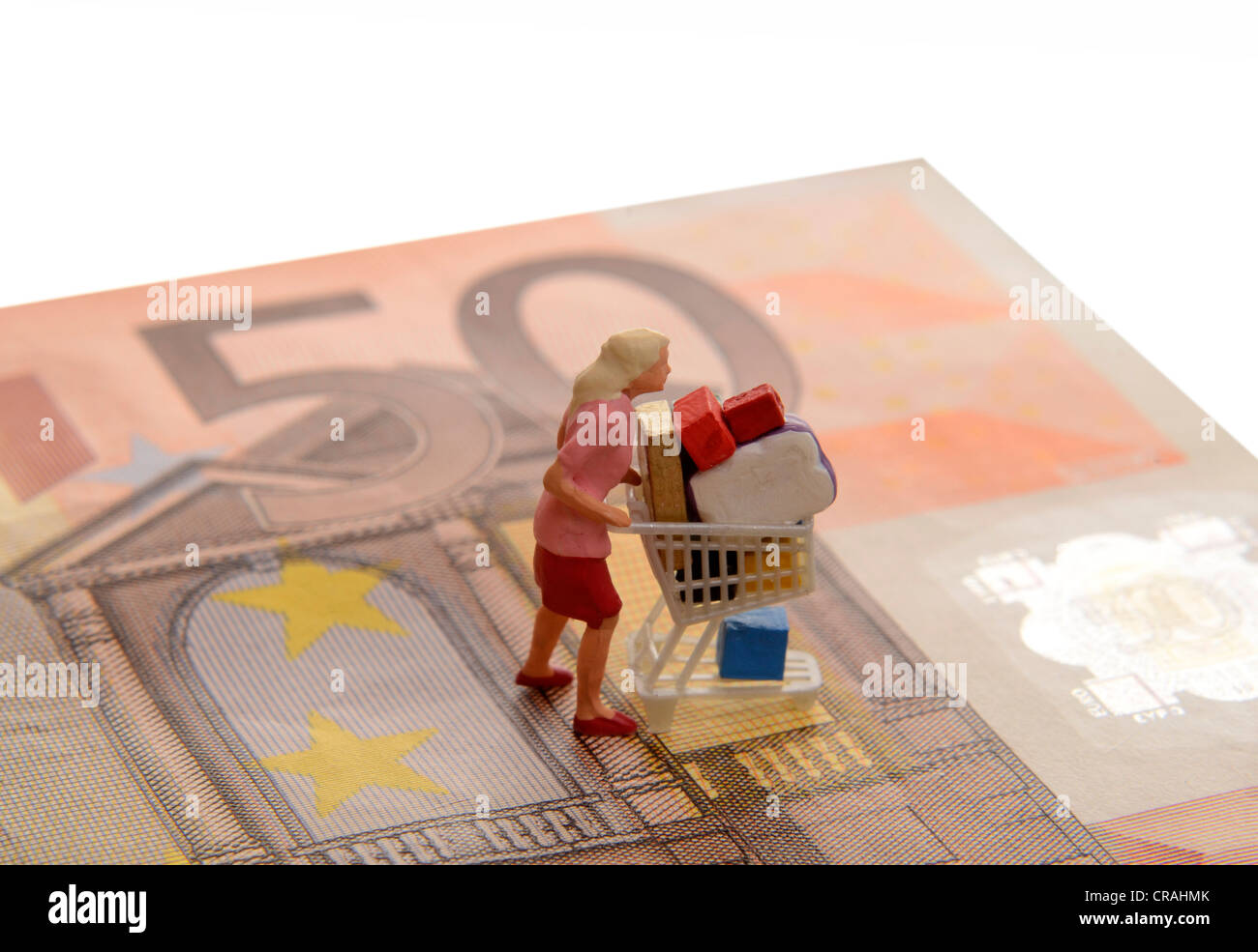 Miniature Woman Figure Pushing An Overflowing Shopping Cart On A 50