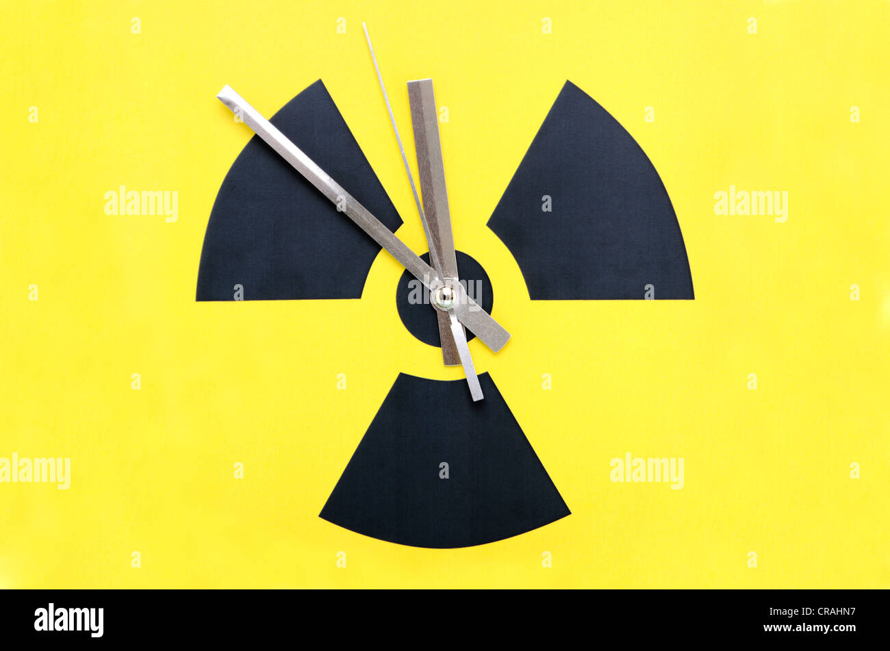 Atomic symbol with clock hands set at 11:55, symbolic image for to phase-out nuclear power - Stock Image