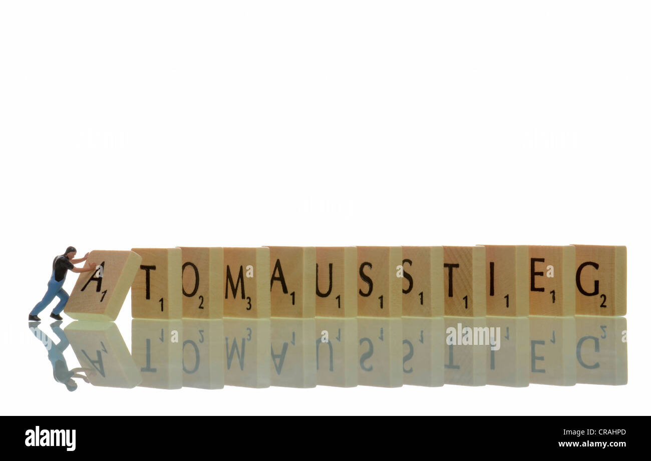 Workers figure toppling a row of letters with the word Atomausstieg or nuclear phaseout, symbolic image - Stock Image