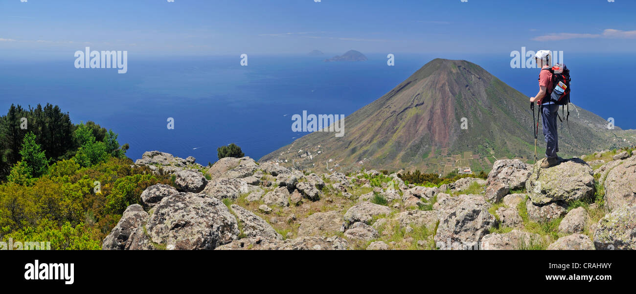 Hiker in front of a volcano on Salina, with the islands of Filicudi and Alicudi at the rear, Aeolian or Lipari Islands, Stock Photo