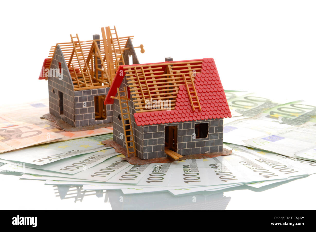 Models of houses under construction on banknotes, symbolic image for mortgage - Stock Image
