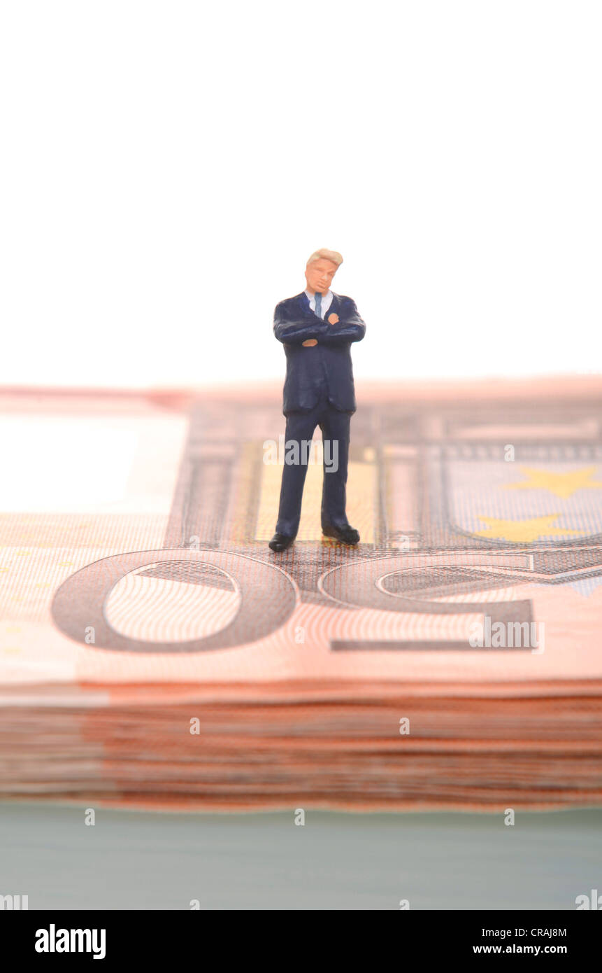 Skeptical-looking businessman, figure standing on a stack of fifty euro banknotes - Stock Image
