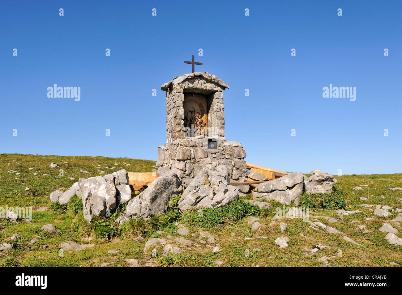 Wayside cross with a small altar and statues of saints on the high plateau Alp Sigel, 1730 m, in the Appenzell Alps - Stock Image