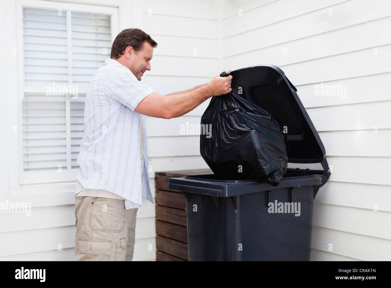 Man taking out garbage - Stock Image