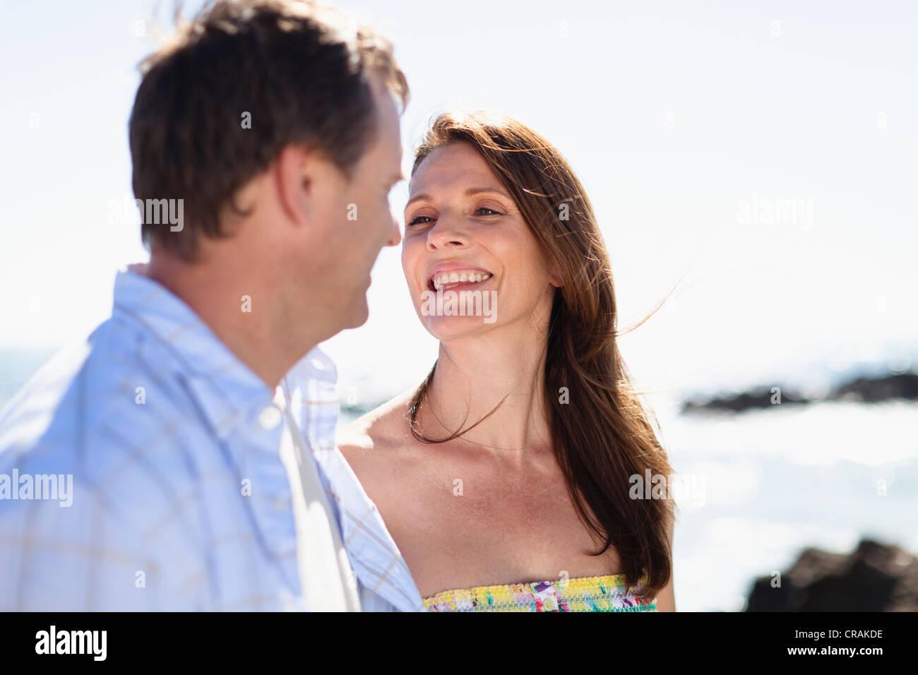 Smiling couple walking outdoors - Stock Image