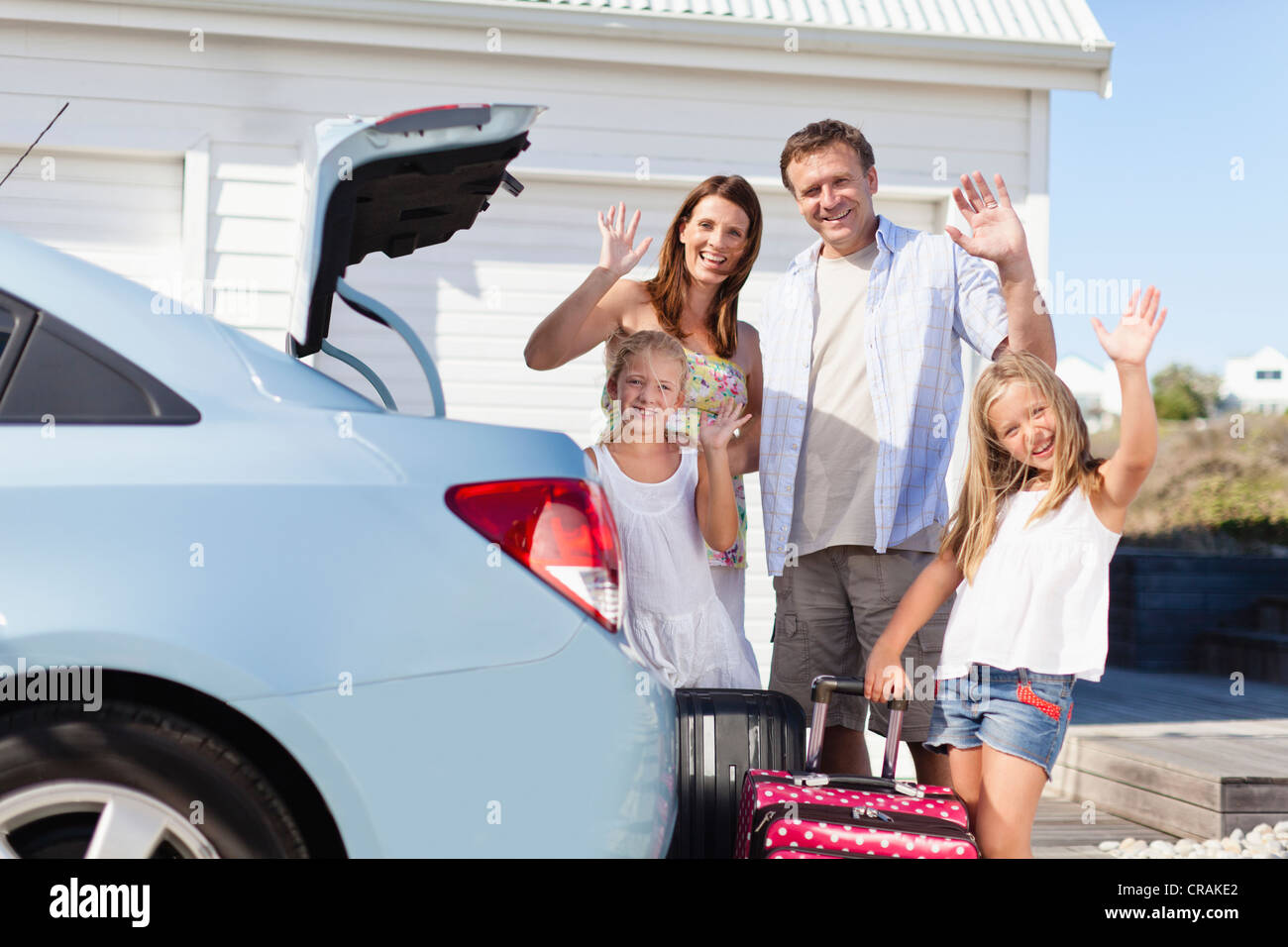 Family loading up car trunk for vacation - Stock Image