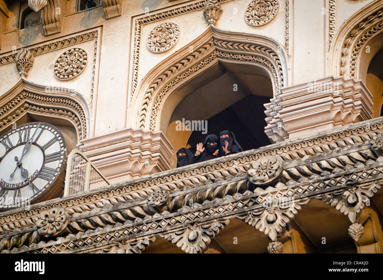 Muslim women waving down from the Charminar monument, Hyderabad, Andhra Pradesh, India, Asia - Stock Image