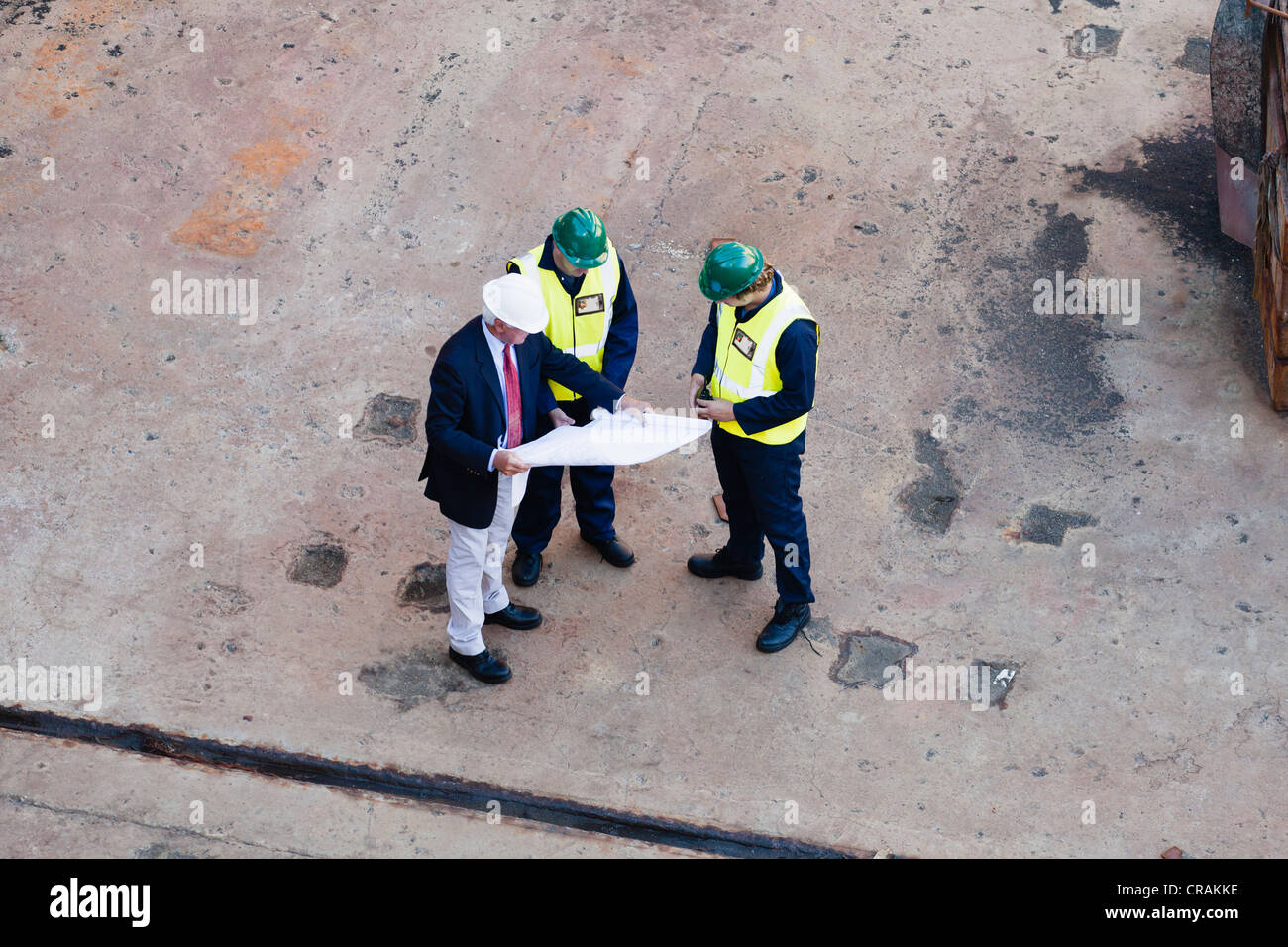 Workers reading blueprints at dry dock Stock Photo