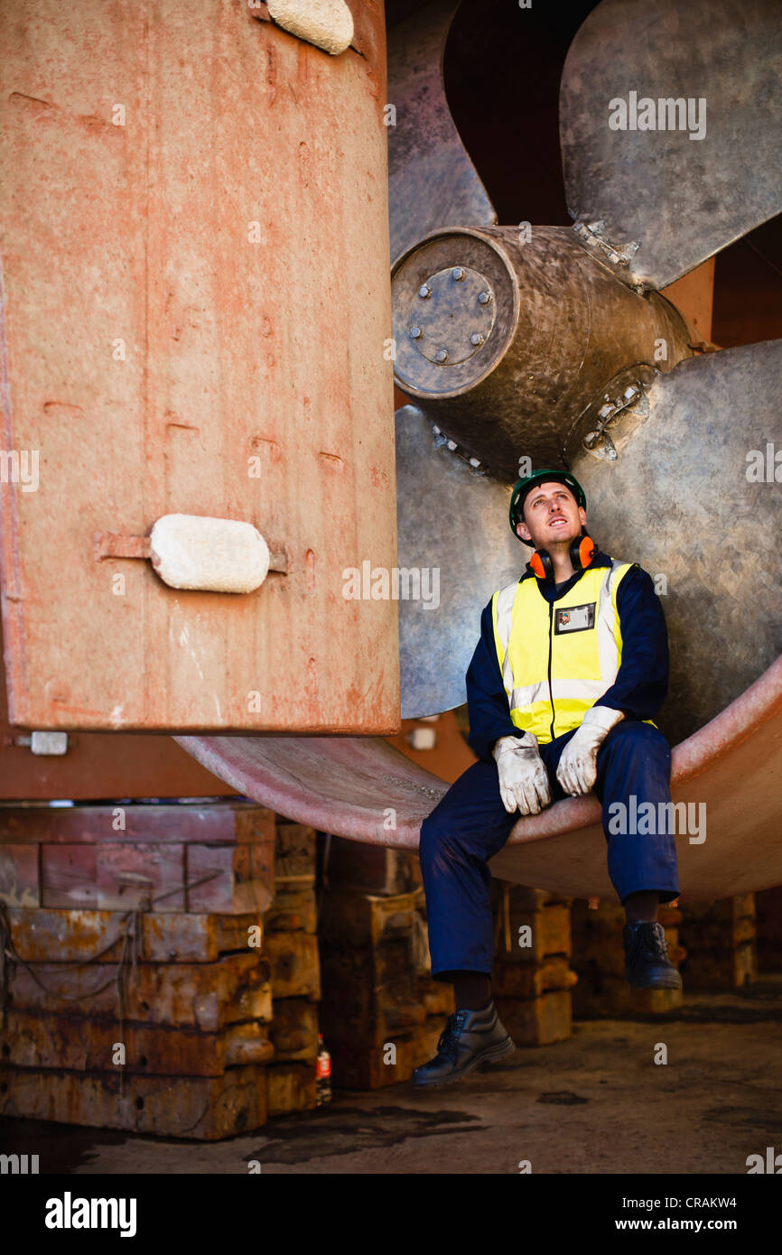 Worker sitting in propeller on dry dock - Stock Image