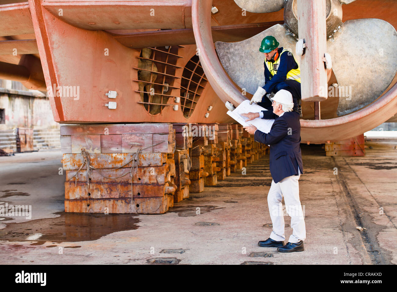 Workers talking in propeller on dry dock Stock Photo