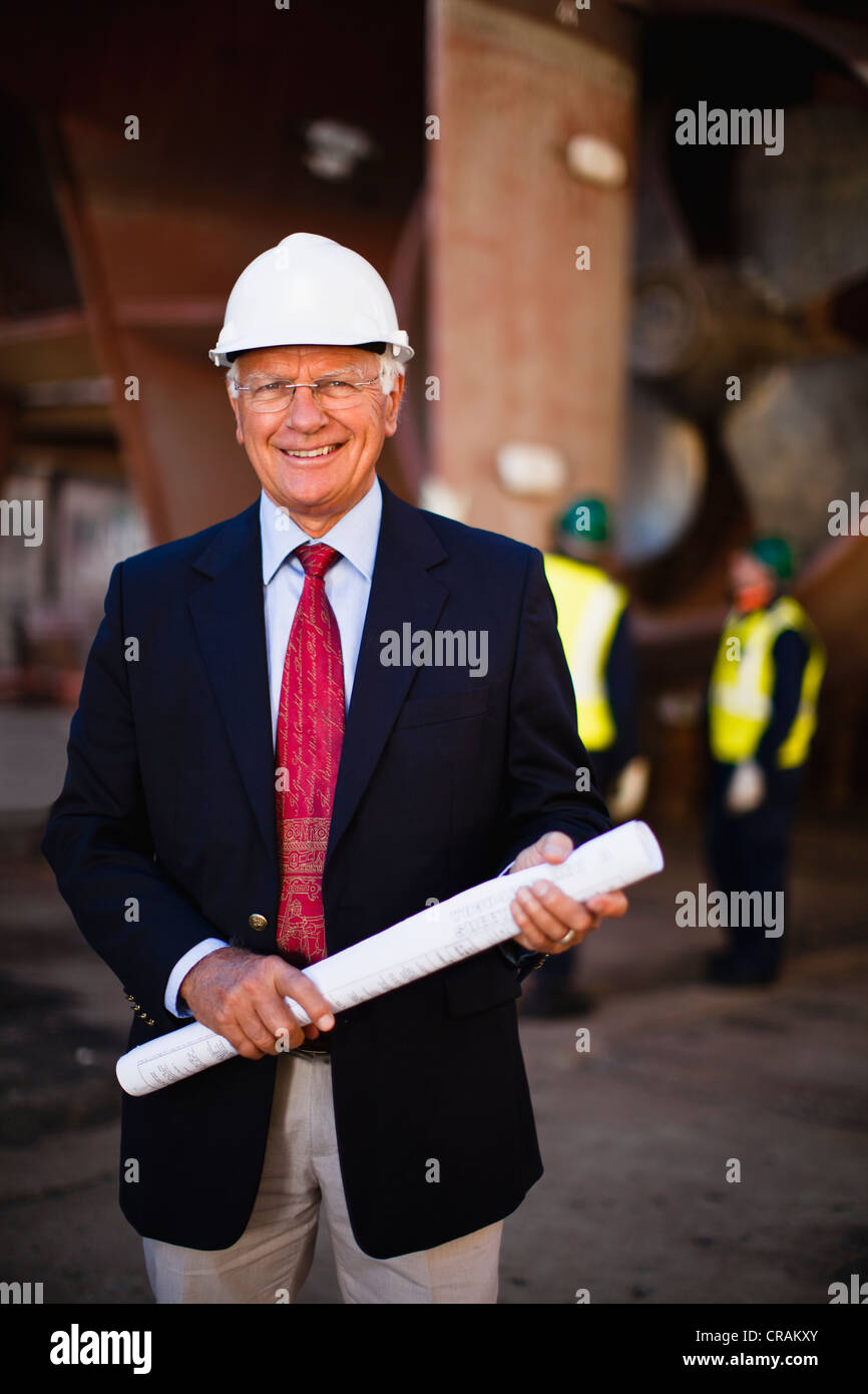 Businessman with blueprints on dry dock - Stock Image