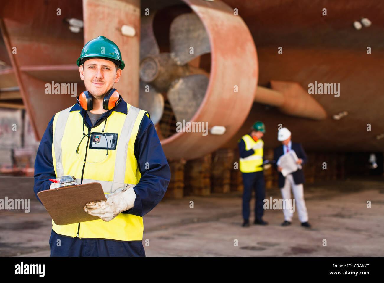 Worker carrying clipboard on dry dock - Stock Image